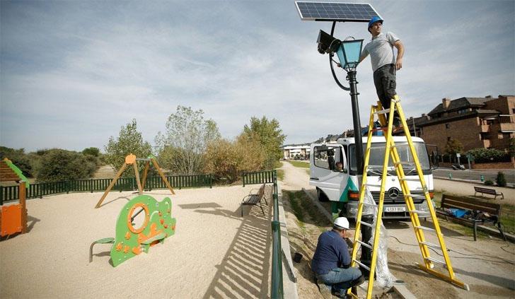 Ayuntamiento de Las Rozas instala 9 farolas solares con tecnología LED que no consumen energía eléctrica. Operarios instalando una farola junto a un parque infantil.