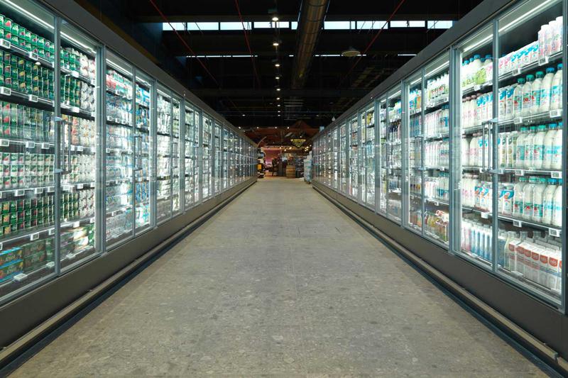 Pasillo de supermercado con vitrinas de refrigeración.