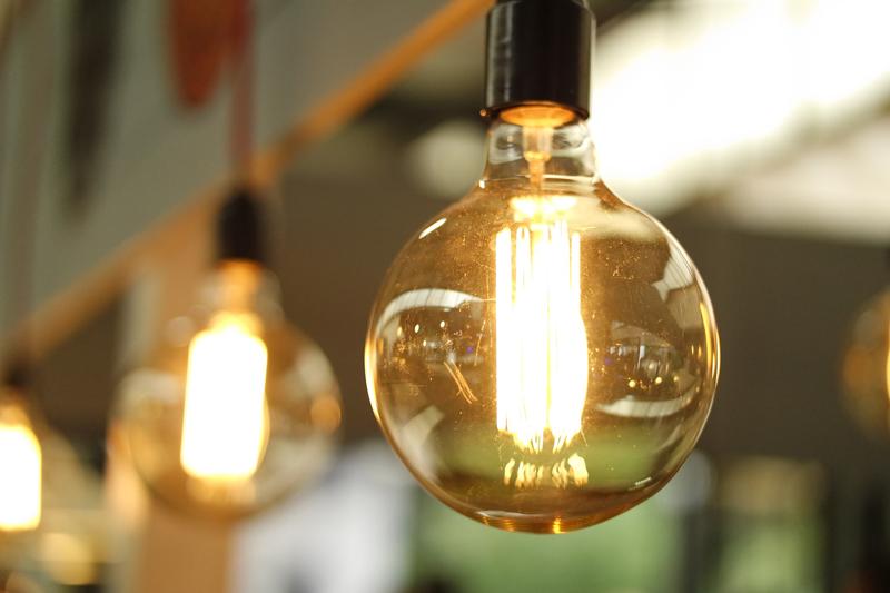 Hilera de bombillas encencidas. Consumo de electricidad en sector hotelero.