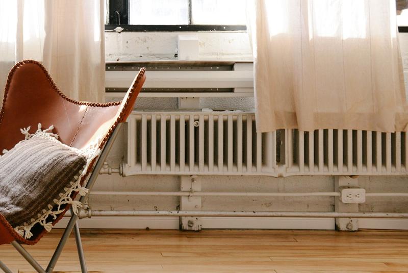 Salón antiguo con un viejo sillón en el centro y radiadores obsoletos en la pared bajo ventanas de madera.