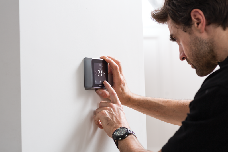 Usuario manipulando un termostato Lyric T6 de Honeywell.