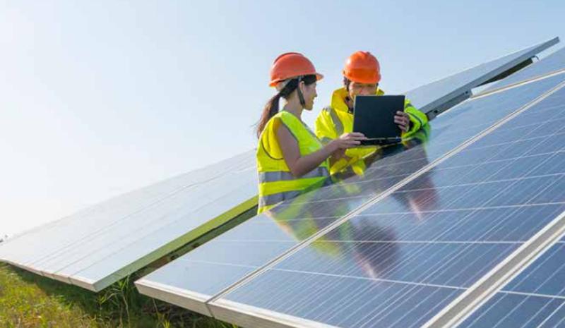 Un hombr y una mujer trabajan junto a un panel fotovoltaico.