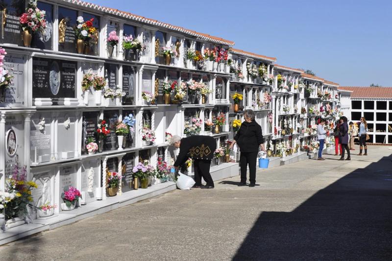 Cementerio de Badajoz. Nichos y mujeres colocando flores.