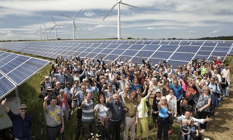 Los nuevos consumidores, prosumidores,, junto a un parque fotovoltaico y aerogeneradores eólicos al fondo.