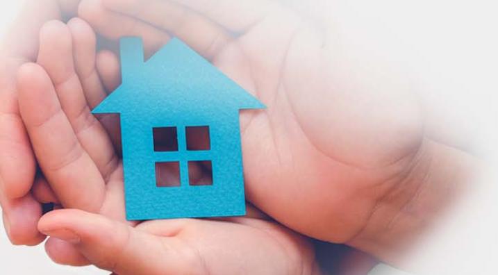 Dos manos de adulto una e infantil la otra protegen una casa .