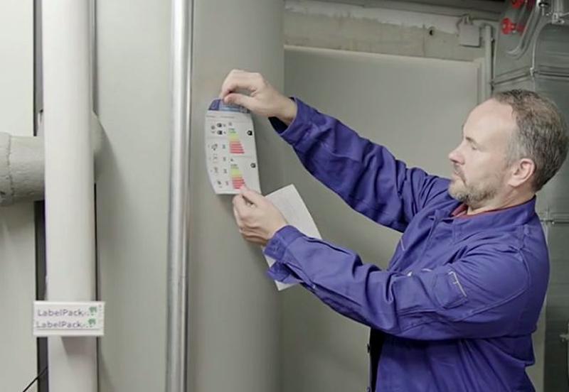 Instalador pegando etiqueta de eficiencia energética en un sistema de calefacción.