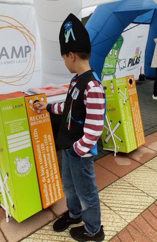 Un niño recicla lámparas en un stand de Ambilamp.