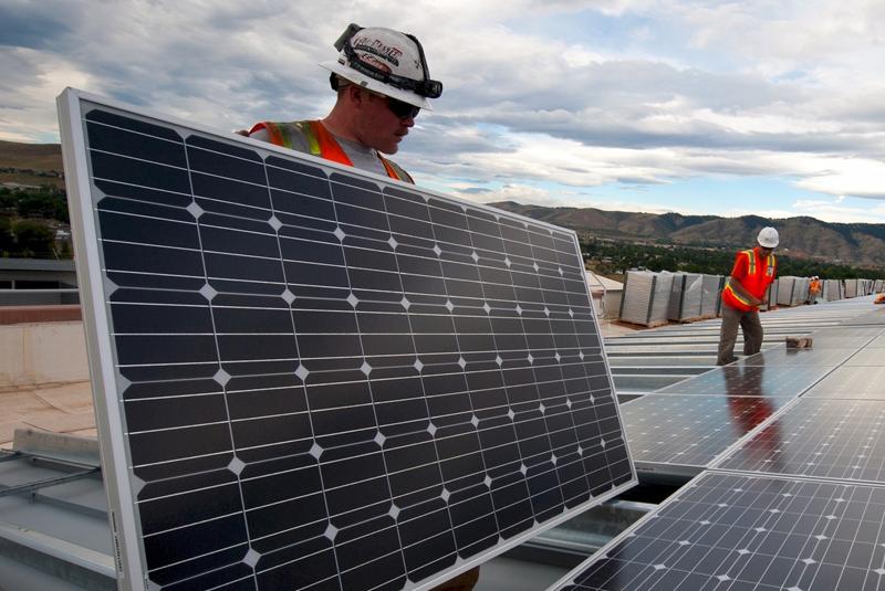 Profesionales instalando placas fotovoltaicas sobre la cubierta de un edificio.