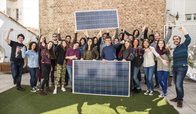 Participantes de Oleada Solar de Ecooo posan ante paneles fotovoltaicos.