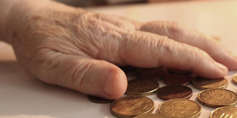 Mano de anciano. Monedas.
