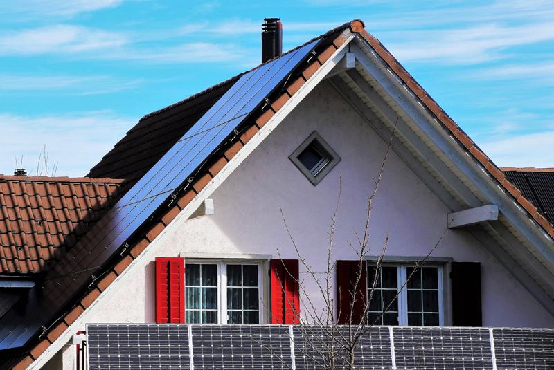 Vivienda con placas fotovoltaicas en balcones y placas de energía solar térmica sobre el tejado inclinado.