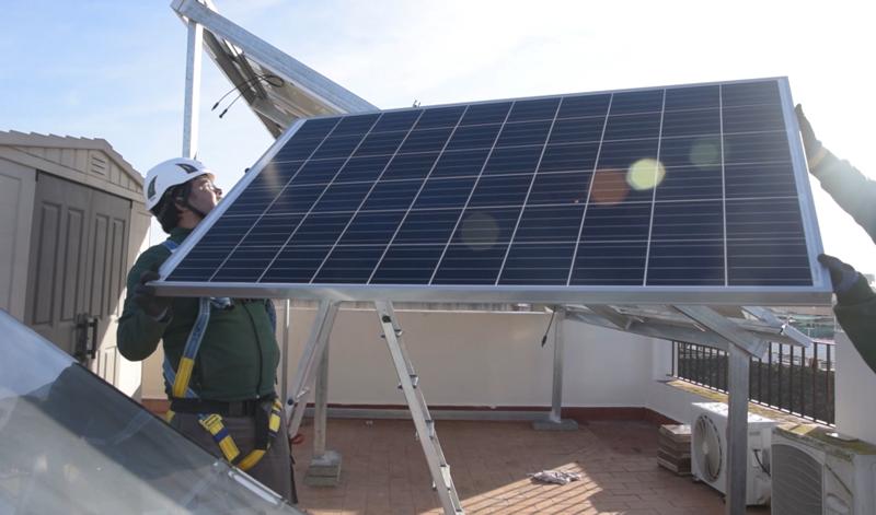 Profesional instalando panel fotovoltaico en una azotea. . Junta de Andalucía. Ayudas para el autoconsumo y la eficiencia energética.