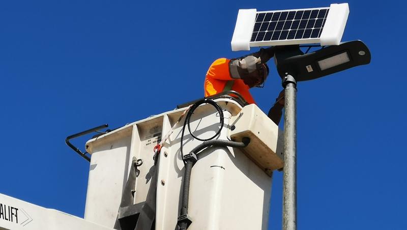 Operario municipal instalando luminaria LED con paneles fotovoltaicos.